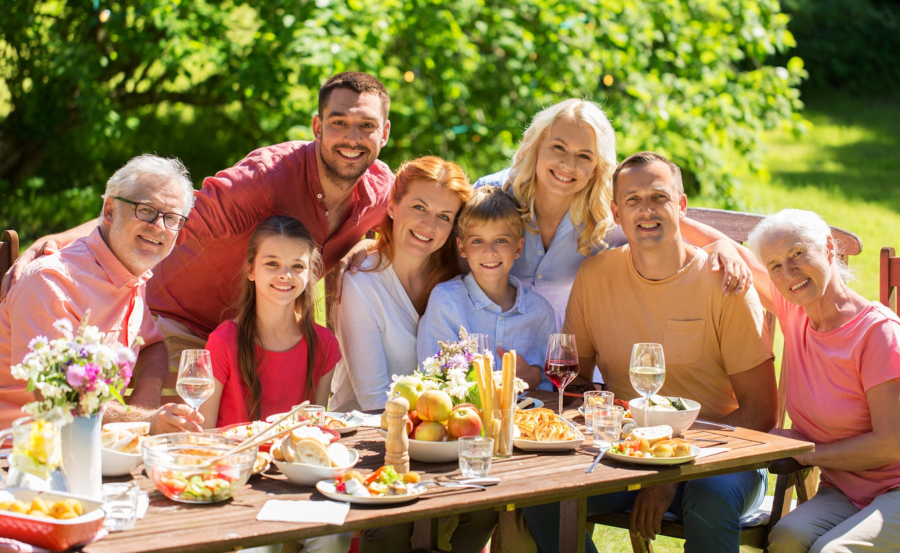 A multi-generational family, happily toasting over an outdoor lunch